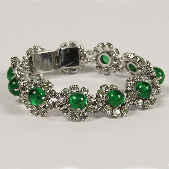 Costume jewelry at its finest, this 1973 Christian Dior bracelet features linked florets with green cabachon stones surrounded by clear glass diamond petals in a silver tone setting. Measures: Length 7 inches.